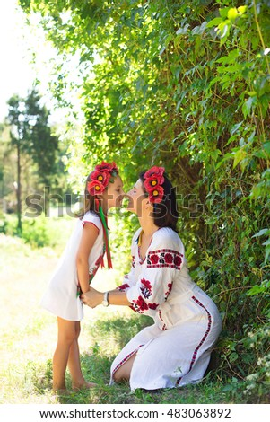 Bright picture of hugging mother and daughter in national Ukrainian costume
