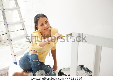 bright picture of lovely housewife painting at home - stock photo