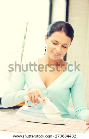 bright picture of lovely housewife with iron - stock photo