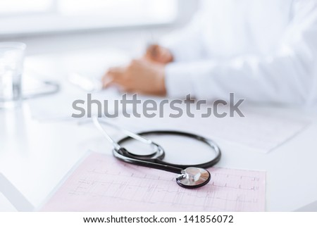 bright picture of male doctor hands with cardiogram - stock photo