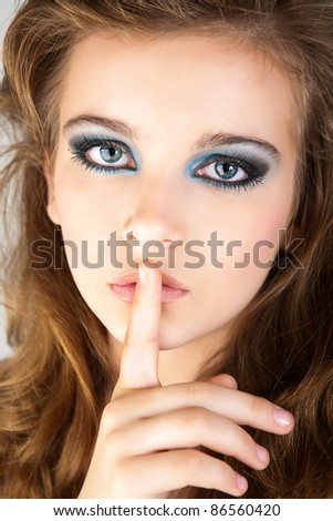 bright picture of young woman with finger on lips. - stock photo