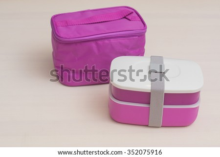 Bright pink lunchbox with two sections for taking away dinner for school and office - stock photo