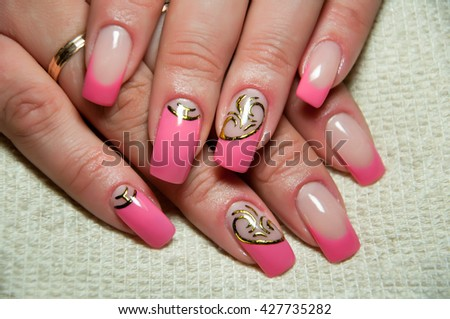 bright pink manicure with an exclusive gold pattern - stock photo