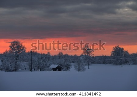 Bright pink sunset over snowcovered winter countryside with a cottage - stock photo