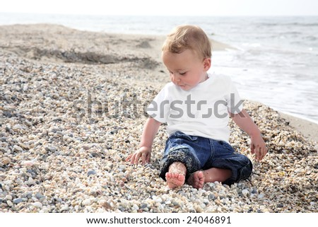 bright portrait of a sweet baby boy on the beach - stock photo