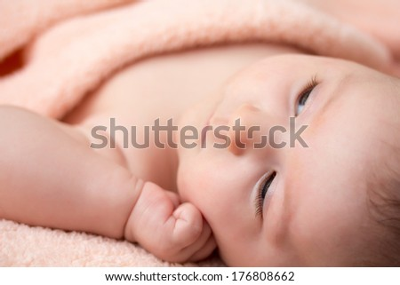 Bright portrait of adorable thinking newborn baby girl