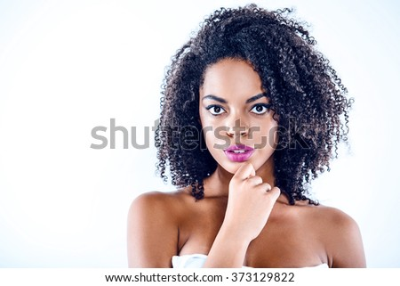 Bright portrait of beautiful young mixed race woman with curly hair on white background. Girl looking at camera - stock photo