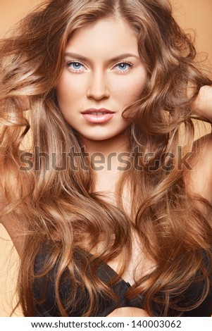 bright portrait of lovely young woman with freckles demonstrating her curls - stock photo