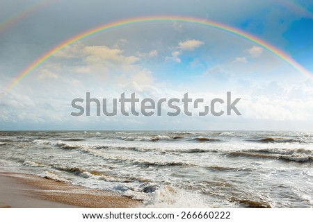 Bright rainbow in the sky with clouds above the ocean - stock photo