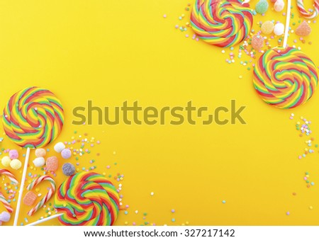 Bright rainbow lollipop candy on colorful yellow wood table for Halloween Trick or Treat or Childrens Party.  - stock photo