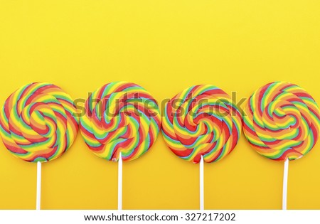 Bright rainbow lollipop candy on colorful yellow wood table for Halloween Trick or Treat or Childrens Party.