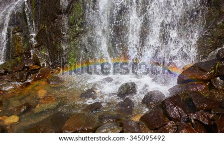 Bright rainbow on a background of water falls - stock photo