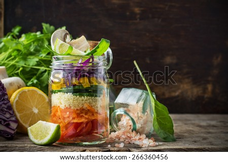 Bright rainbow salad  of tomatoes, carrots, pepper, red cabbage, arugula and mushrooms with butter and sea salt on a pink background vegetables and herbs. Trends in healthy eating. Selective focus. - stock photo