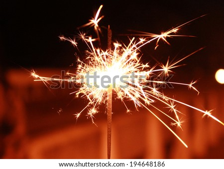 Bright Real Sparkler with A Construction in The Background  - stock photo