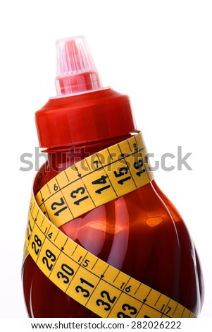 Bright red bottle of ketchup with yellow tape measure on a white background closeup, vertical photo - stock photo