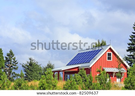Bright red building with solar panels on the metal rooftop on a mostly sunny summer day in a public park. - stock photo