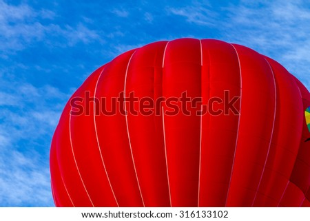 Bright red colored hot air balloon against blue morning sky on the ground before take off - stock photo
