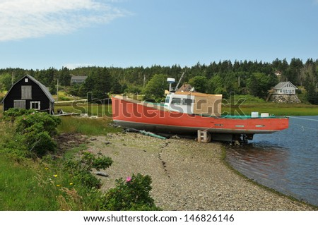 Bright red fishing boat at the shore in eastern Nova Scotia - stock photo
