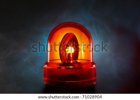 Bright red police light glows through a foggy night - stock photo