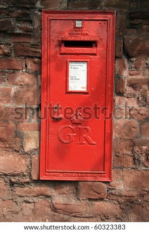 bright red postbox in old crumbling wall