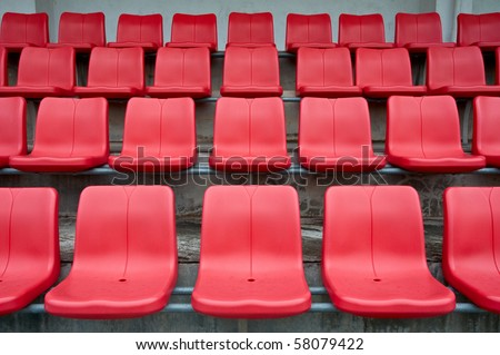 Bright red stadium seats on the stand - stock photo