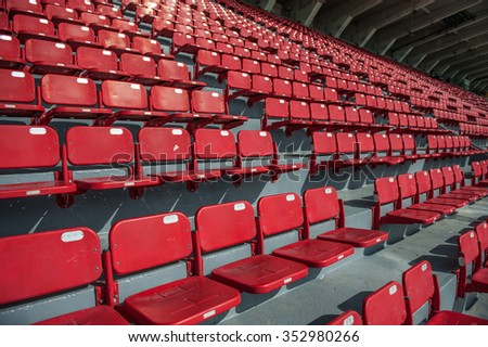 Bright red stadium seats on the stand in a large international soccer stadium