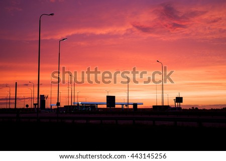 Bright red sunset and silhouettes lampposts. Geometry lanterns at sunset. Industrial landscape.