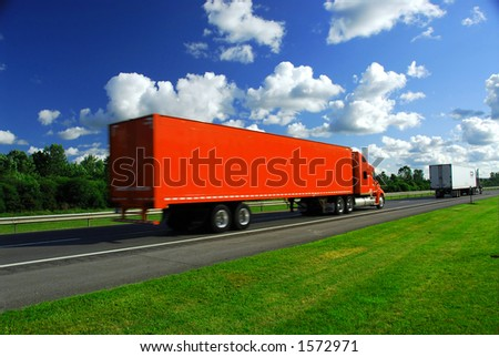 Bright red truck on road, blurred because of fast motion - stock photo