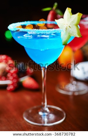 bright refreshing cocktails: blue margarita on a table in a restaurant with creative decoration of salt on the edge of the glass with fruit slices and berries. soft focus - stock photo