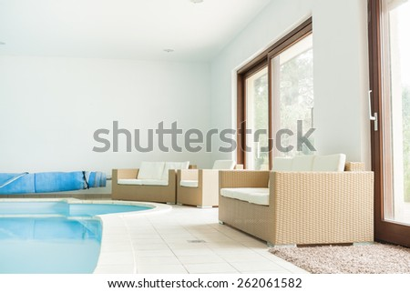 Bright relax room with big swimming pool and comfortable chairs - stock photo