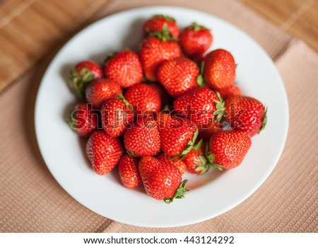bright, ripe, delicious strawberries in a white plate on a wooden background - stock photo