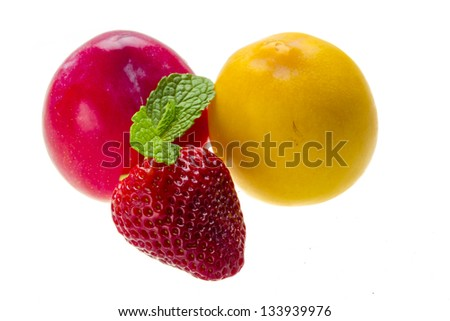 Bright ripe strawberry and plums - stock photo