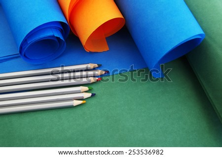 Bright rolls of color paper with colored pencils close up - stock photo