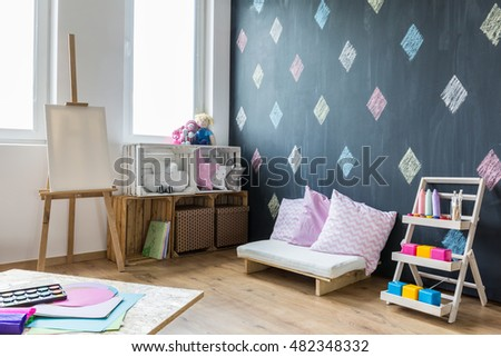 Bright room with easel, painting tools, cushions and wall with the diamond theme