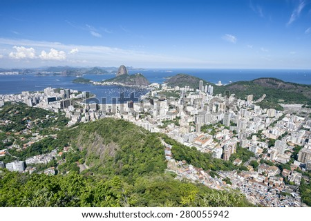 Bright scenic overlook of Rio de Janeiro city skyline with Sugarloaf Mountain, Botafogo, Guanabara Bay and the nearby favela Dona Marta community - stock photo