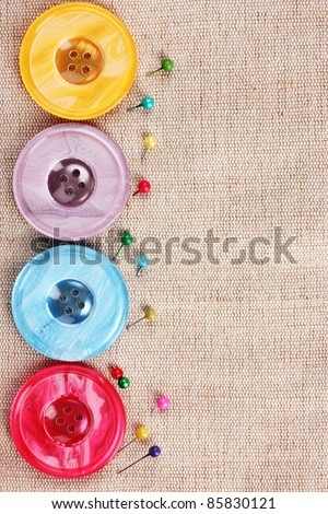 Bright sewing buttons on gray fabric