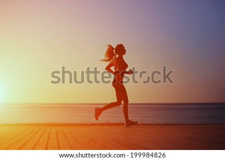 Bright silhouette of athletic female runner with a beautiful figure runs on the wooden pier on the sea and sky background, morning jog on the beach - stock photo