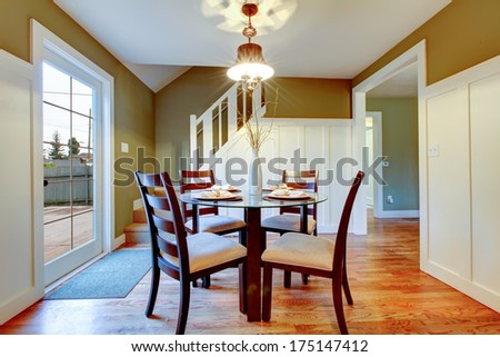 Bright small dining area with walkout deck. Hardwood floor, white stairs and olive wall complete the refreshing look of the interior