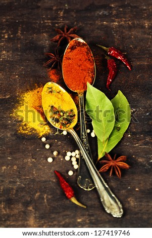 Bright spices on an old  wooden board - stock photo