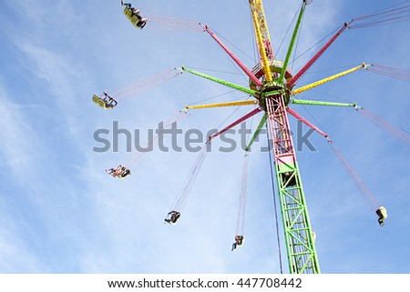 Bright still life of large flying high carousel ride machine turning against the blue sky in a fun fair festival park on a sunny day, outdoors. Dynamic movement recreational go around ride, exterior. - stock photo
