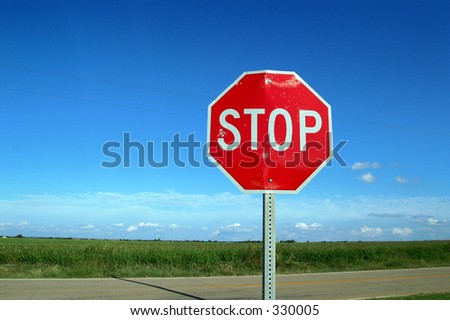 Bright stop sign in a country road - stock photo