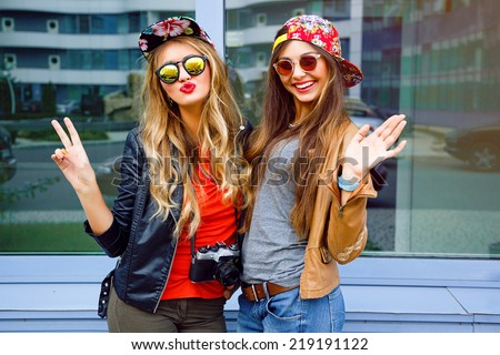 Bright stylish lifestyle urban portrait of two pretty best friends girls posing at leather jackets bright swag hats and sunglasses. Having faun, send you kiss and say hello. - stock photo