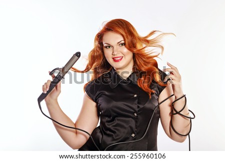 Bright stylish red-haired woman in professional attire. Barber, hair stylist Holding a curling iron and curl makes - stock photo