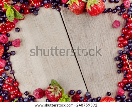 Bright summer frame of fresh sweet berries on the table - stock photo