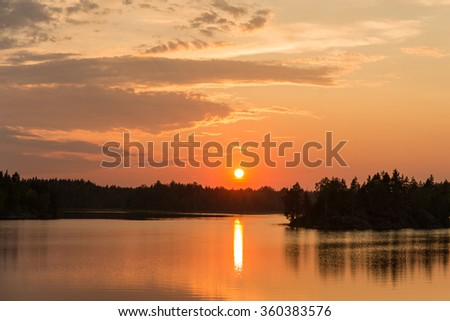 bright summer sunset over the lake in the woods - stock photo