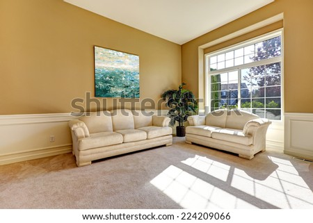 Bright sun room interior with large french window and light tones sofa and love seat - stock photo