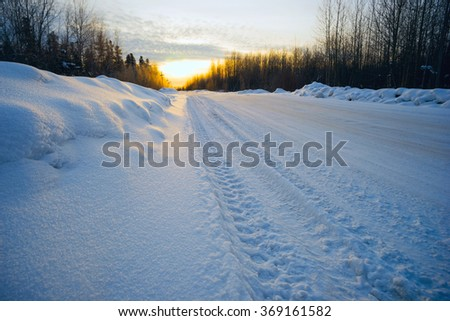 Bright sun  sunset in winter snow-covered road . - stock photo