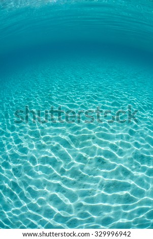 Bright sunlight ripples across a sandy seafloor in the tropical Pacific Ocean. - stock photo