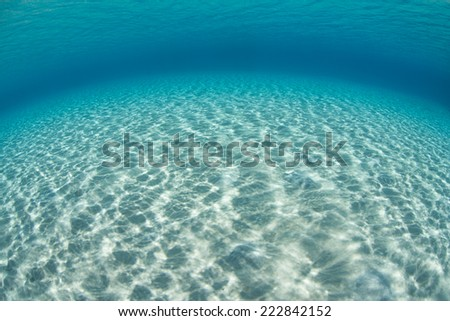 Bright sunlight shines on a shallow sand flat in the tropical Pacific Ocean.  - stock photo