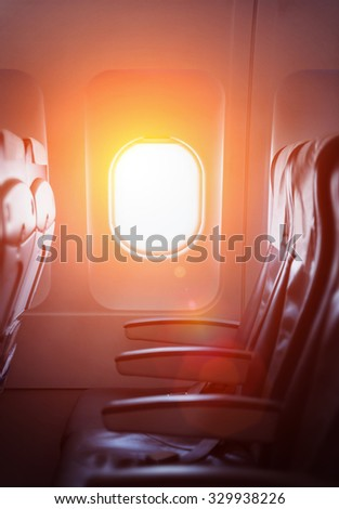 Bright sunlight through airplane window  and standard, coach passenger seats on interior of aircraft.